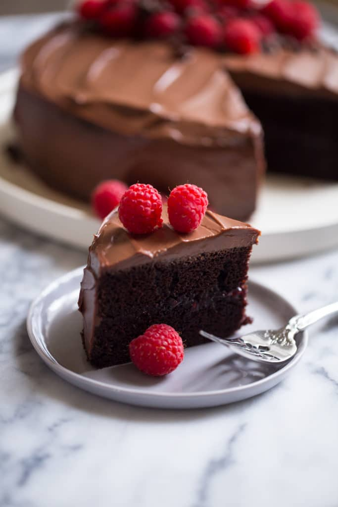 slice of chocolate cake on small gray plate with fork