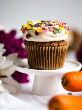 carrot cake cupcakes with tahini cream cheese frosting and sprinkles on a mini cake stand