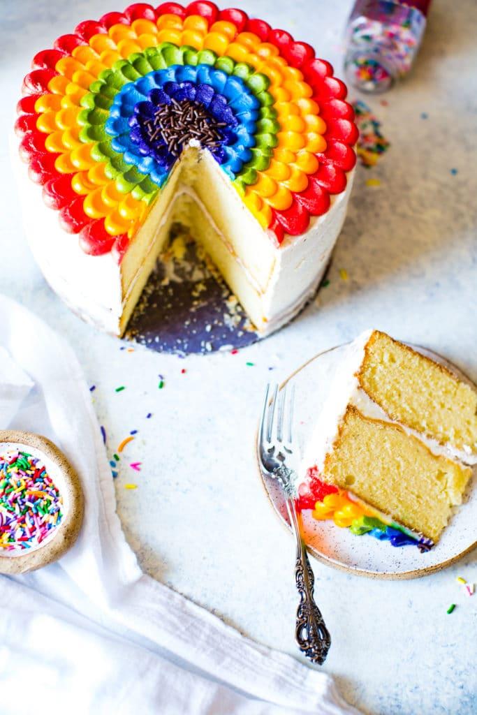 rainbow petal cake with a slice of cake on a plate