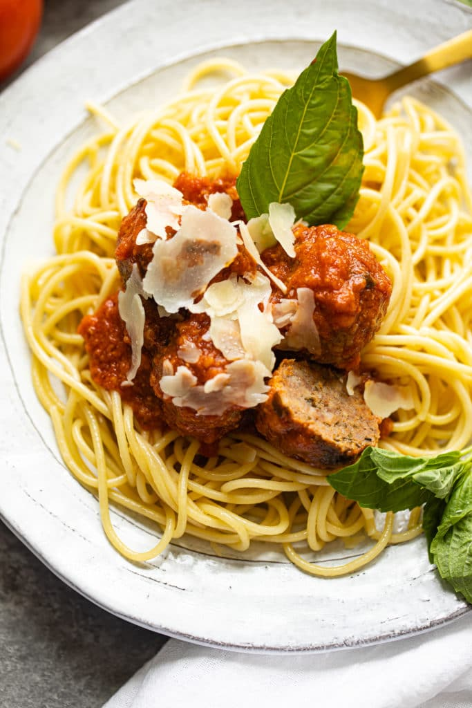 close up shot of spaghetti and meatballs with shaved parmesan on top