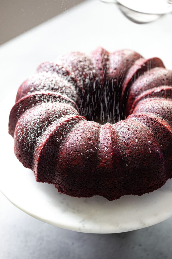 red velvet bundt cake with falling powdered sugar
