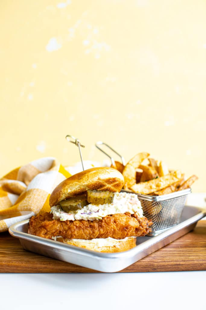 fried chicken sandwich on a wooden board with fries