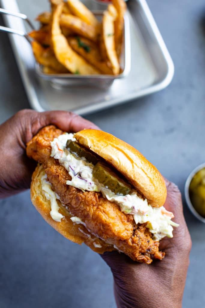 Hands holding a chicken sandwich