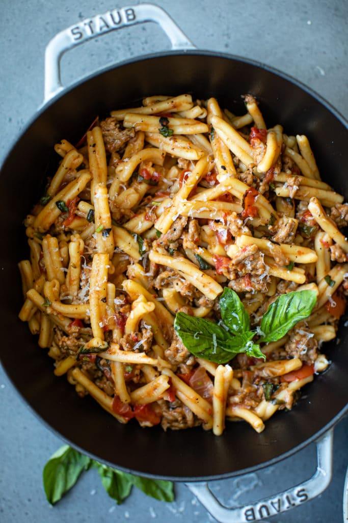 big pot of pasta with basil on top