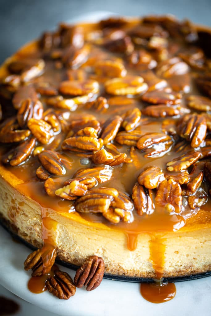 caramel sauce dripping off a cheesecake with pecans on top