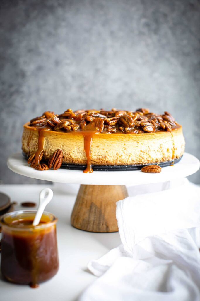 caramel pecan cheesecake on a wooden marbled cake stand