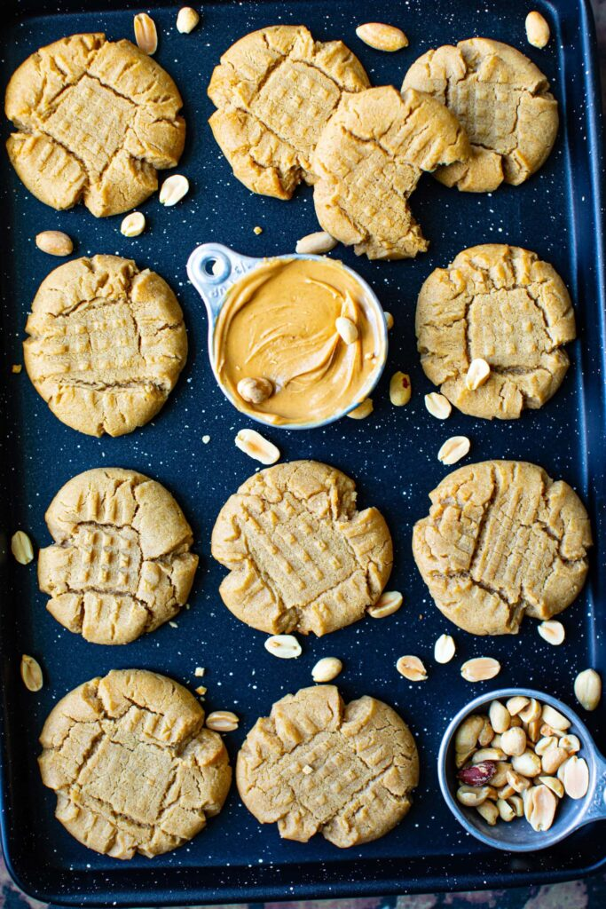 peanut butter cookies on a speckled black sheet pain with crushed peanuts