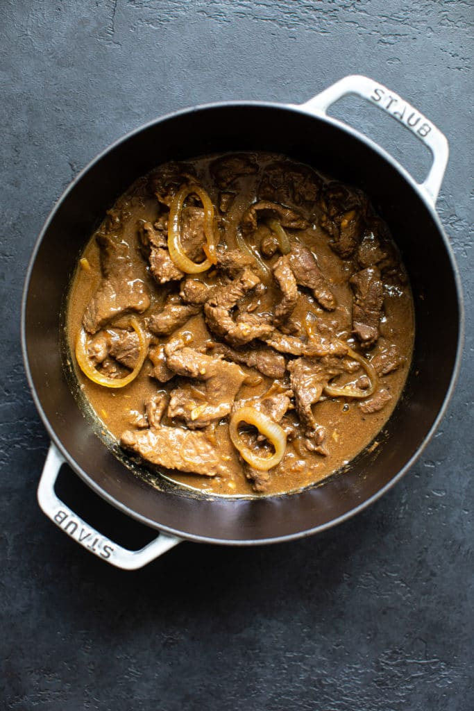 beef and onions in a gray dutch oven pot