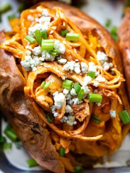 close up shot of a sweet potato filled with shredded chicken and bleu cheese crumbles