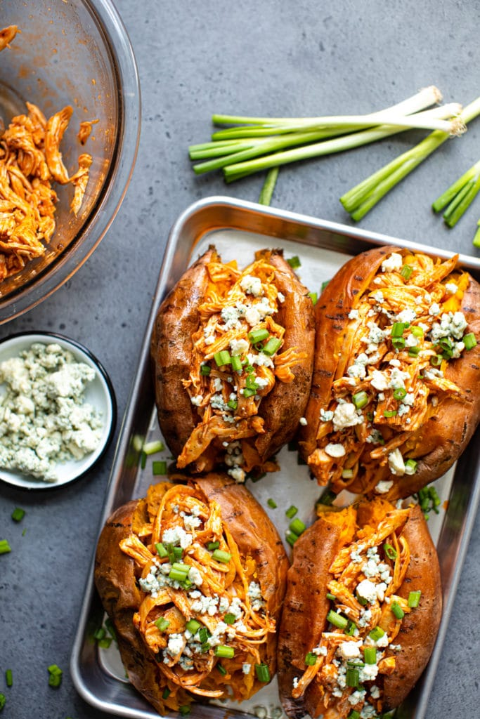 four Buffalo Chicken Stuffed Sweet Potatoes on a silver tray with a bowl of extra shredded chicken
