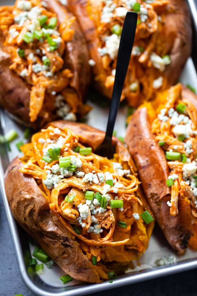 Buffalo Chicken Stuffed Sweet Potatoes on a baking sheet with a black fork in the middle