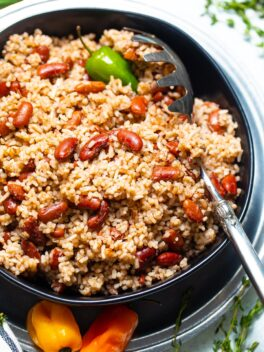 Jamaican rice and peas in black bowl with silver spoon