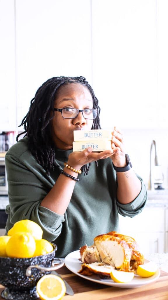 black woman holding sticks of butter