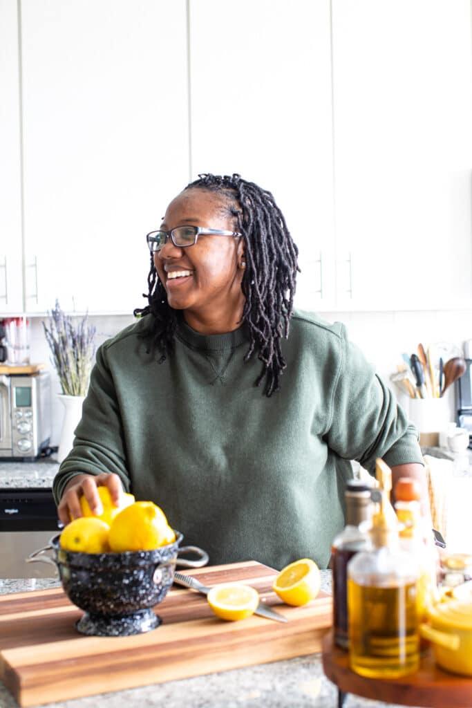 black woman smiling with bowl of lemons