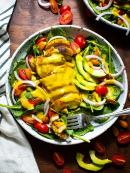 honey mustard dressing on top of spinach salad in bowl with silver fork