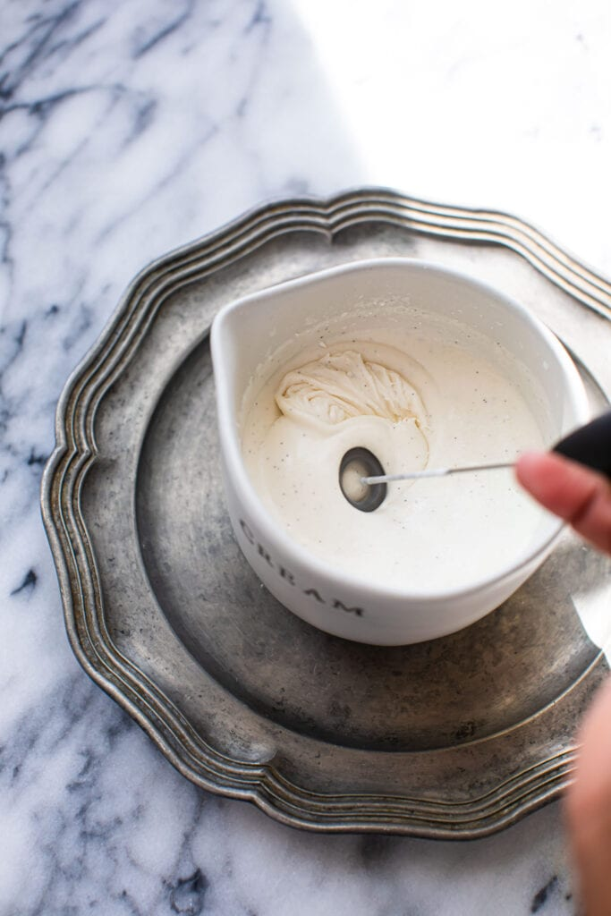hand frothing cream in small white dish