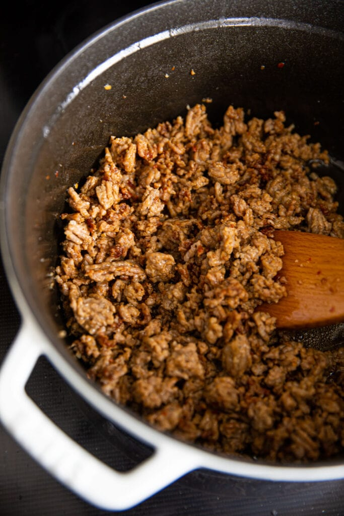 ground meat cooking in large white pot