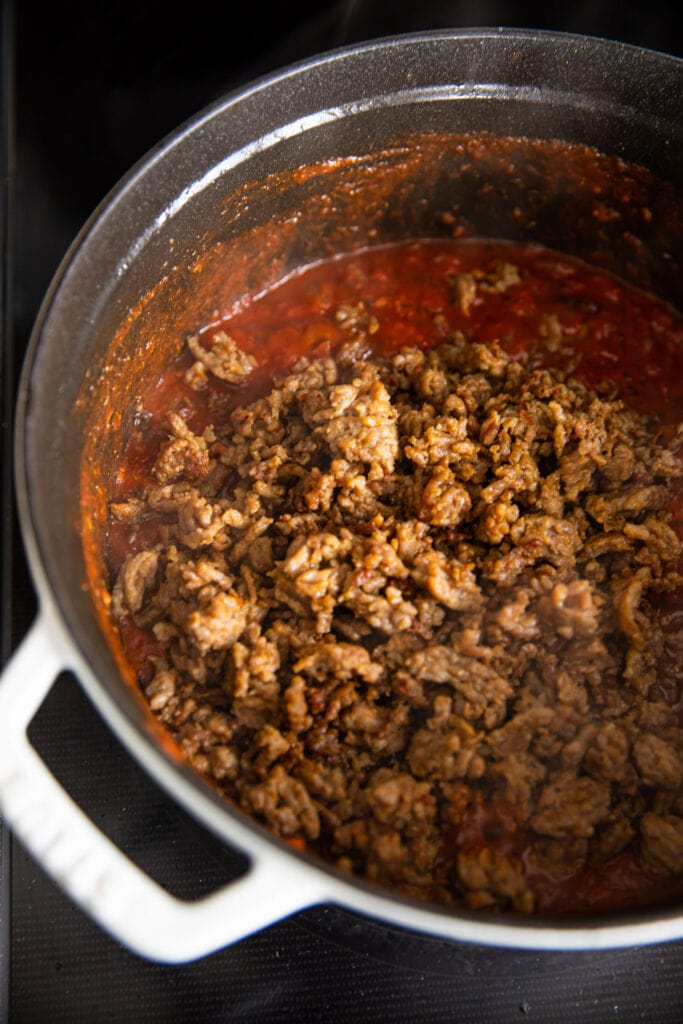 ground meat in meat sauce in large white pot