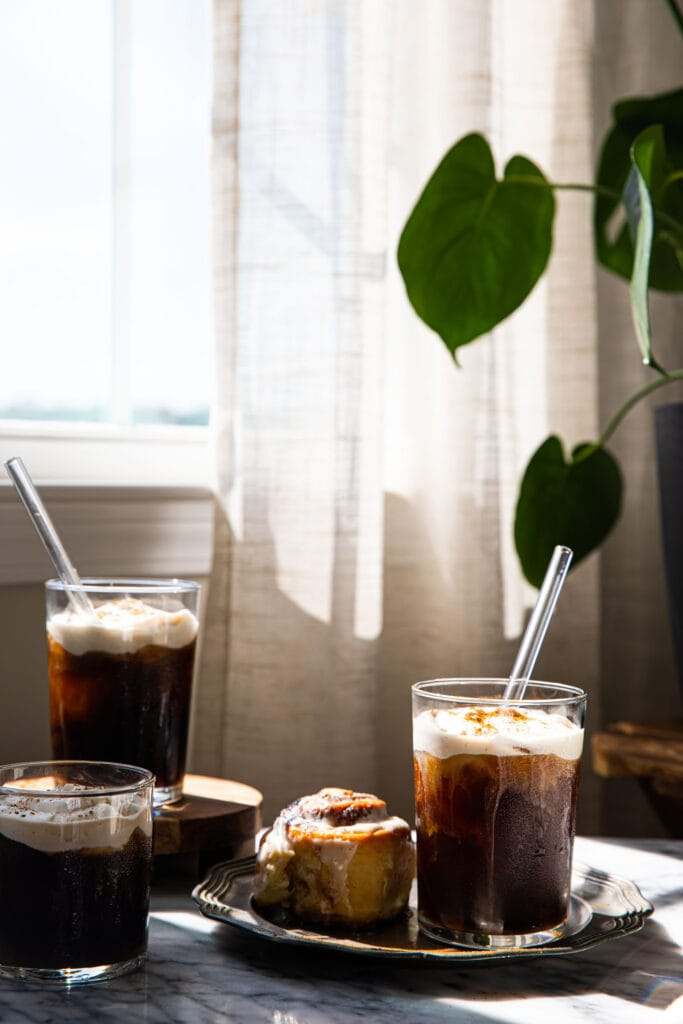 two maple cream cold brews on marble surface with plant in the background