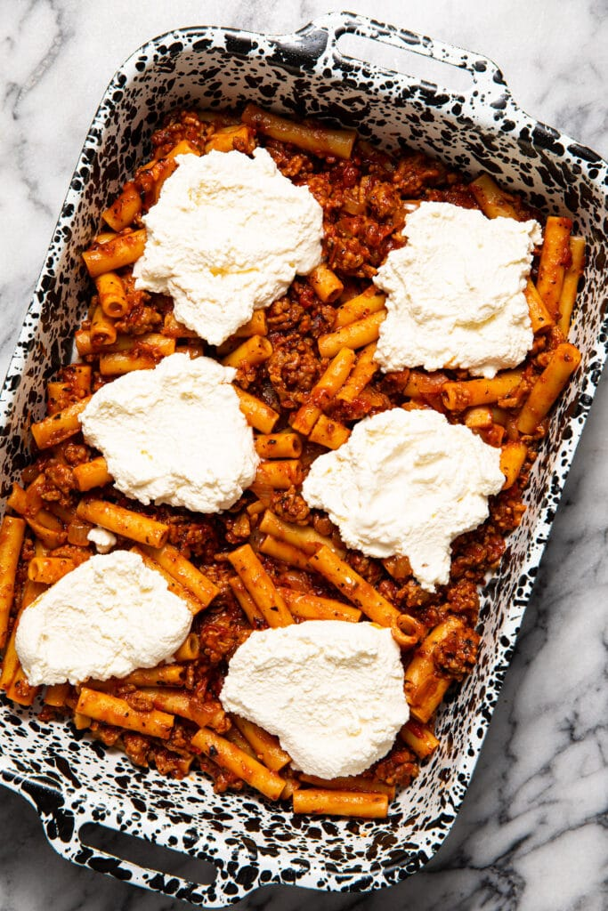 dollops of ricotta cheese on top of baked ziti in baking dish