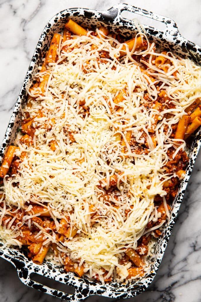 shredded mozzarella cheese on top of ziti pasta in baking dish