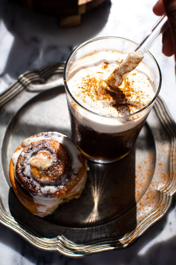 straw in glass of maple cream cold brew with cinnamon roll on silver plate