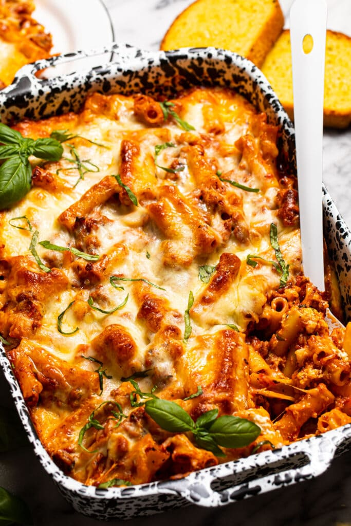 baked ziti in black and white speckled dish with white spoon