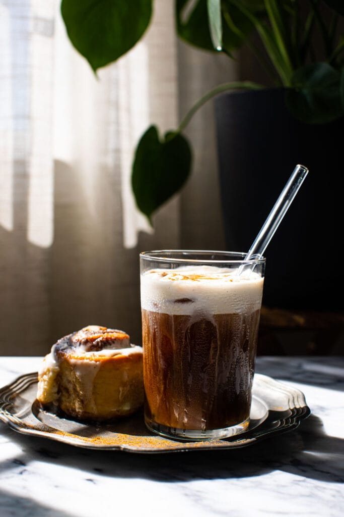maple cream cold brew in glass with cinnamon roll on the side