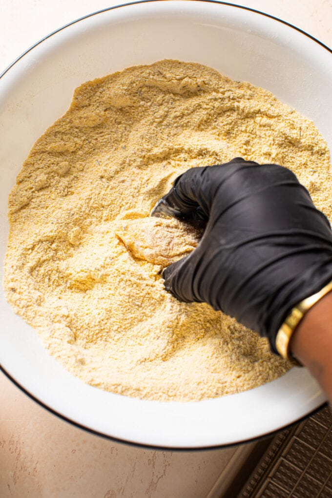 black hand with glove dipping chicken in cornmeal/flour mixture