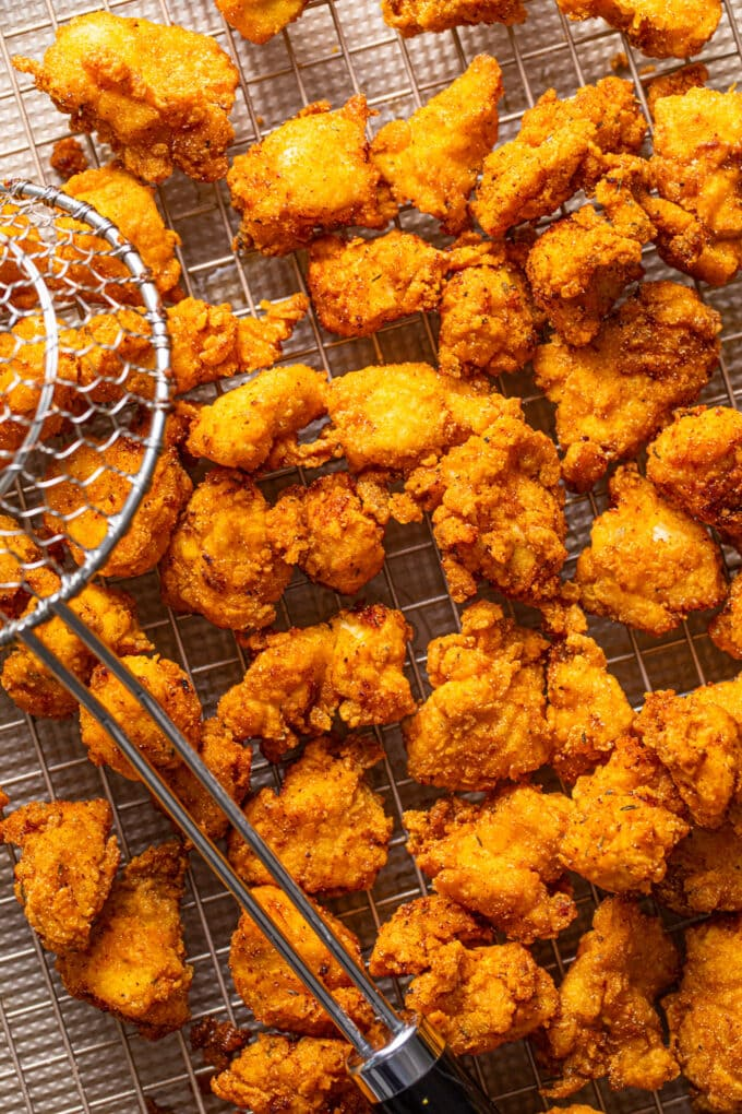 fried chicken pieces with frying spoon on wire rack