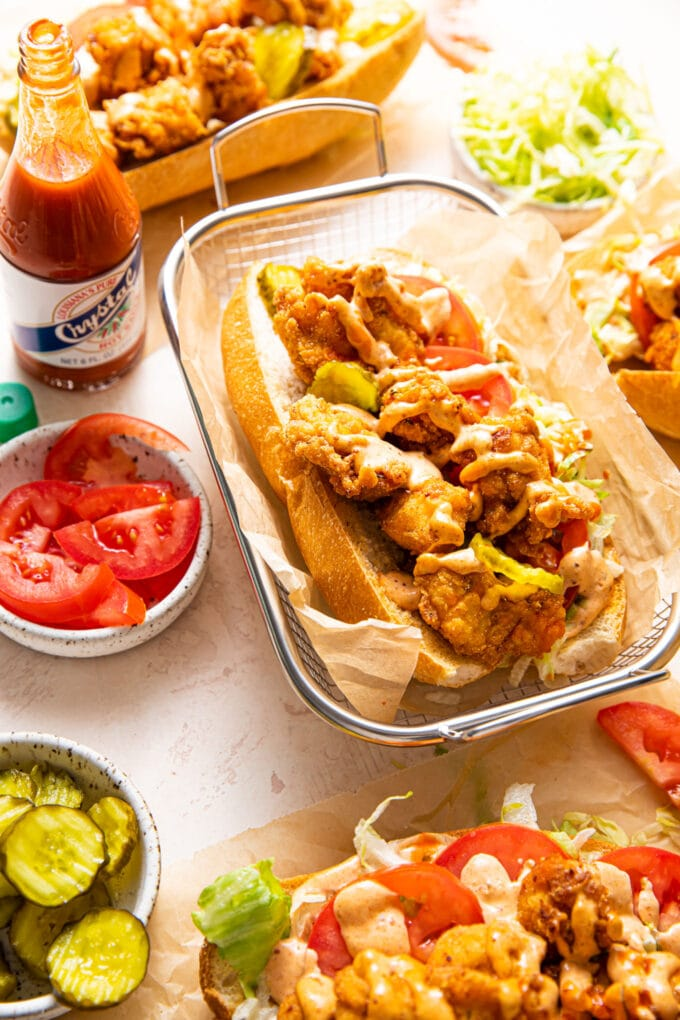 fried chicken po' boys with pickles, tomatoes, and hot sauce on the side