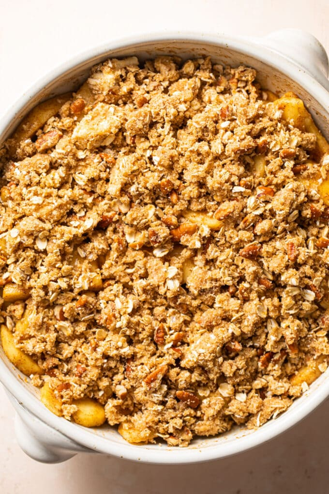 oat topping spread on top of apple filling in casserole dish