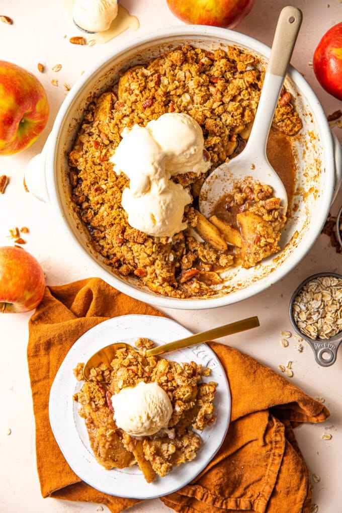 easy apple crisp in casserole dish with small white plate and orange linen on the side