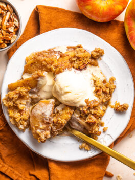 apple crisp with ice cream on top on small white plate with gold spoon