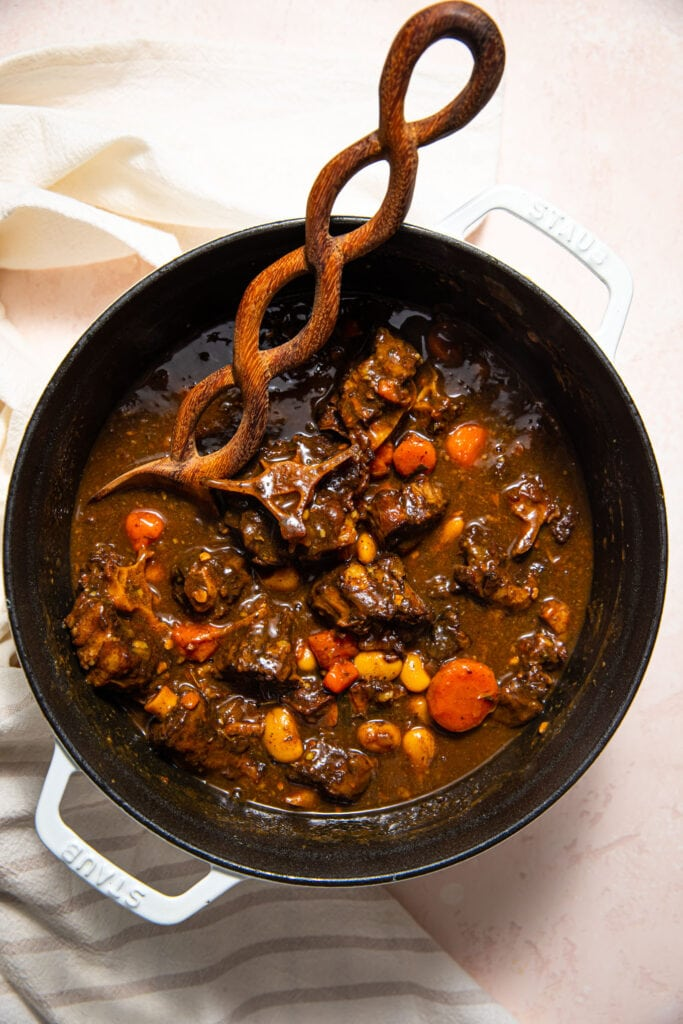 jamaican stewed oxtails in large white pot with wood spoon