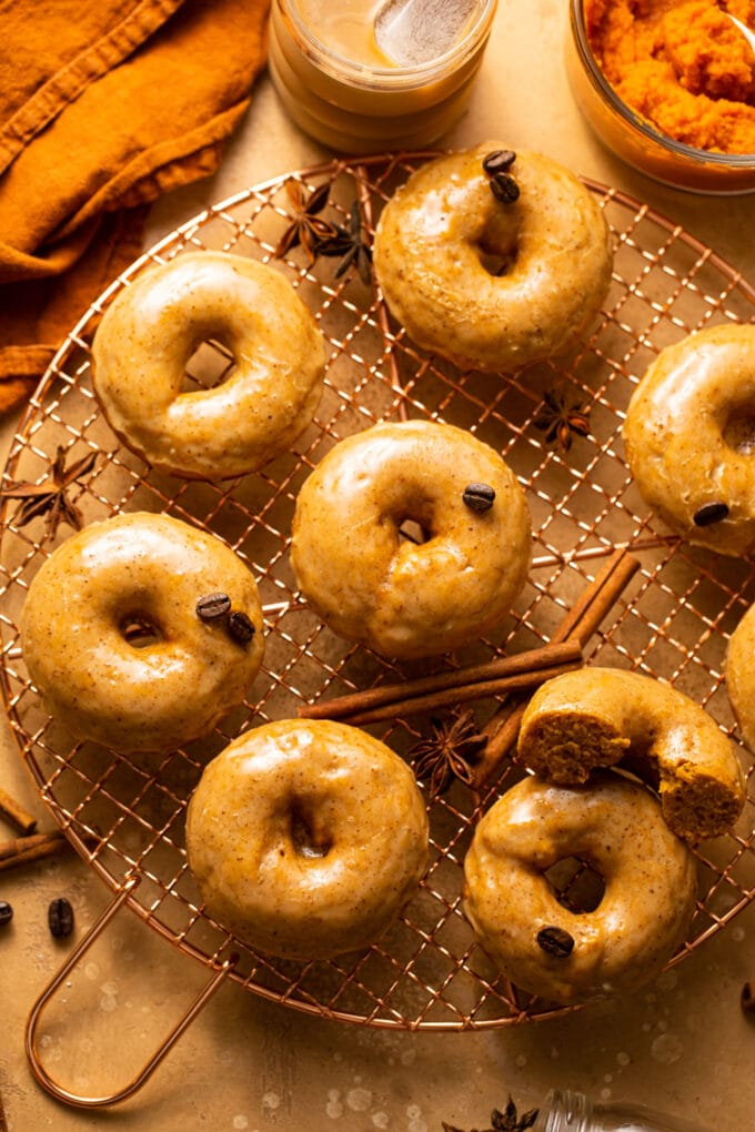 baked pumpkin donuts with coffee glaze on copper wire rack