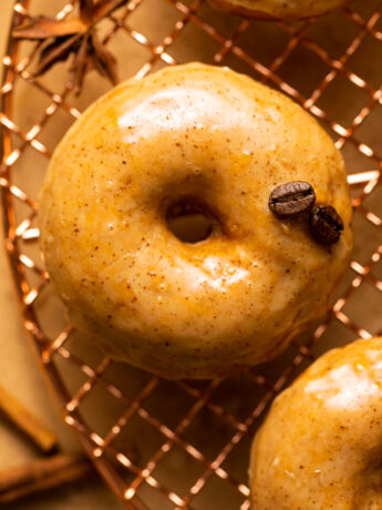 baked pumpkin donut with coffee glaze and espresso beans on top of copper wire rack