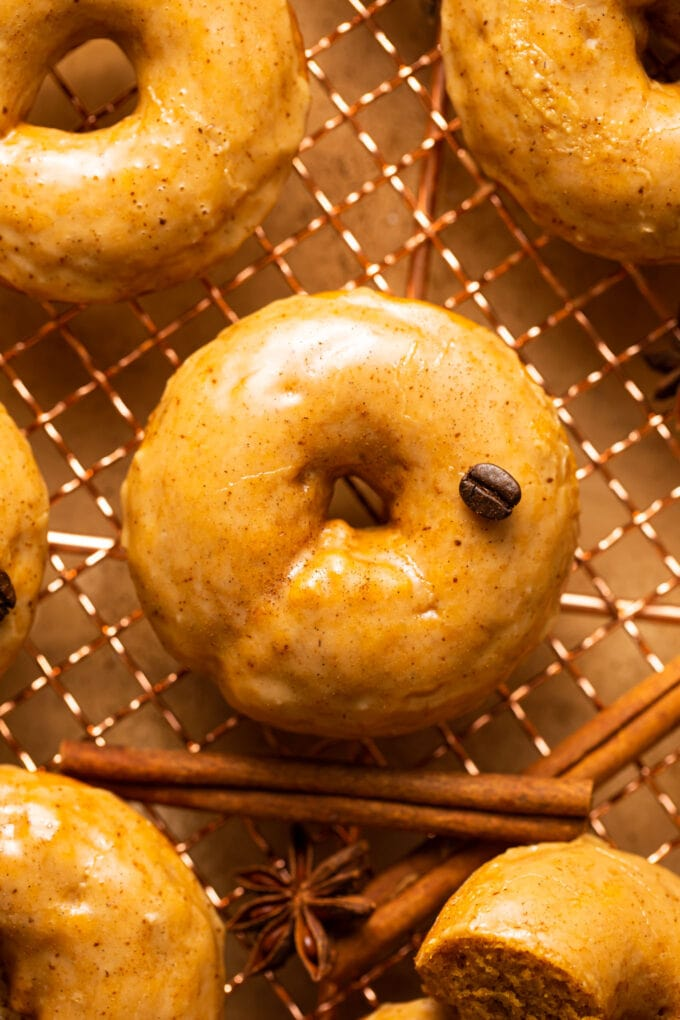 baked pumpkin donut with coffee glaze and espresso bean on top of copper wire rack