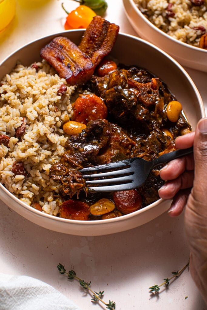 black hand with black fork taking piece of Jamaican stewed oxtails in bowl