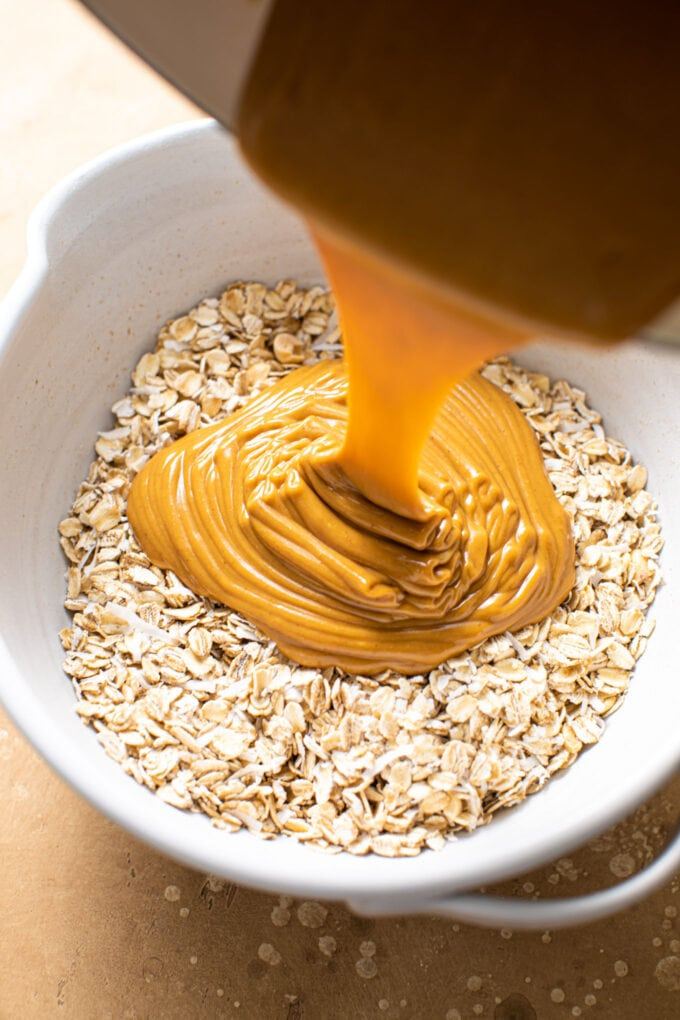 peanut butter sauce being poured into large bowl filled with oats