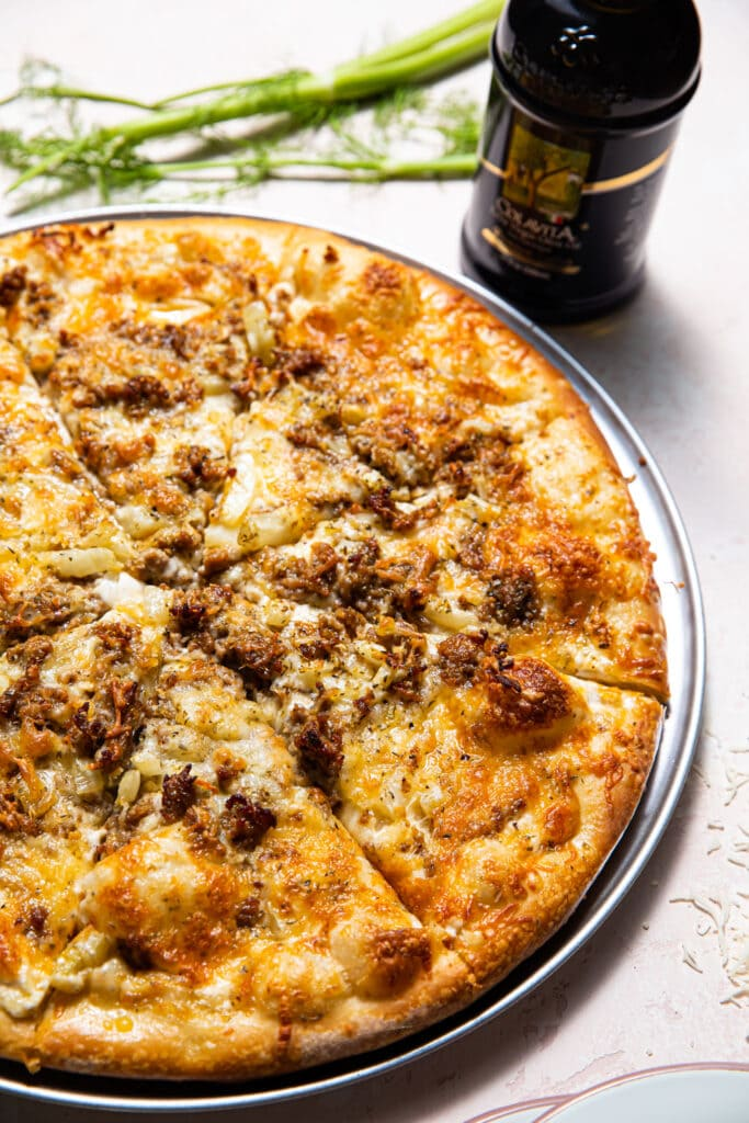 sausage and fennel pizza on silver tray with bottle of olive oil on the side
