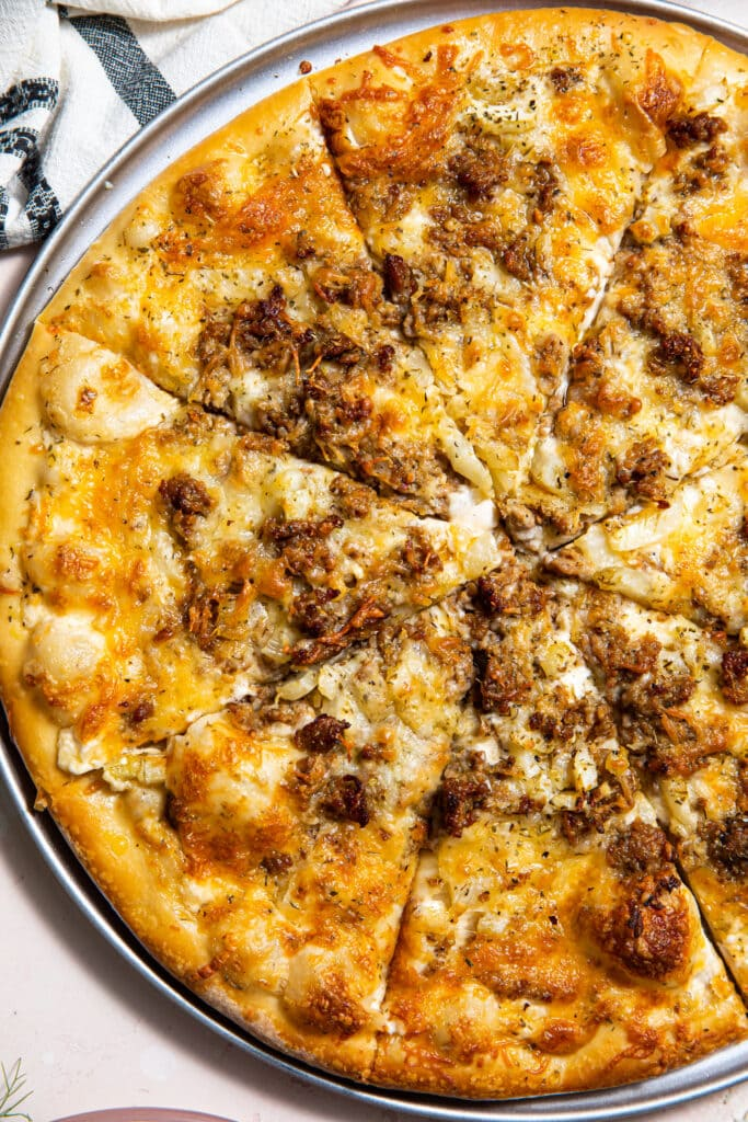 sausage and fennel pizza on silver pizza tray