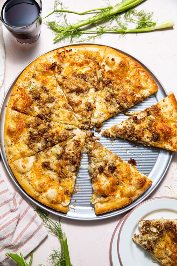 sausage and fennel pizza on silver pizza tray with pink and white plate on the side