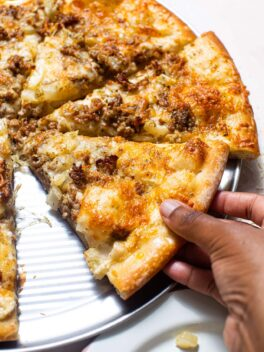black hand grabbing a slice of sausage and fennel pizza