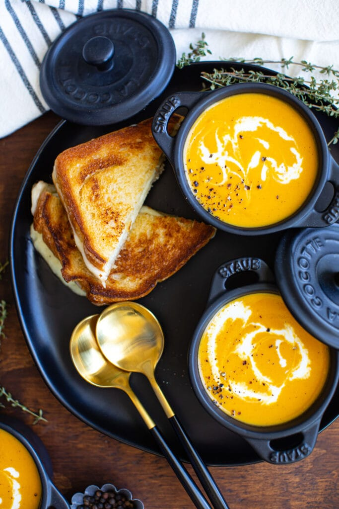 roasted butternut squash soup in mini black ramekins on black plate with grilled cheese