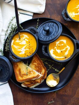 roasted butternut squash soup in mini black ramekins on black plate