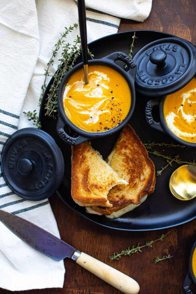 roasted butternut squash soup in mini black ramekins with grilled cheese