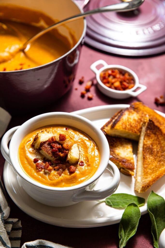 sweet potato soup in white bowl on white oval platter