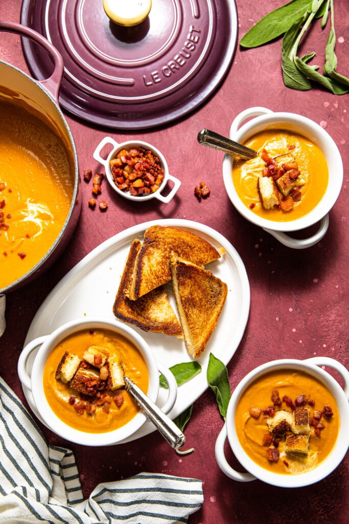 sweet potato soup in bowls on purple surface