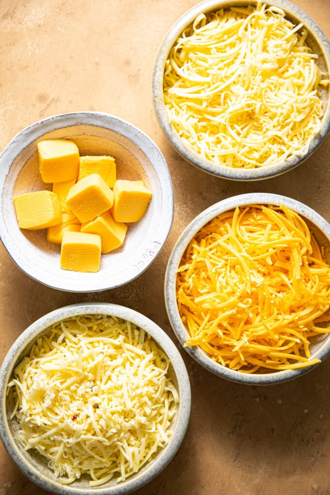different types of cheese for baked Mac and cheese in bowls on beige surface